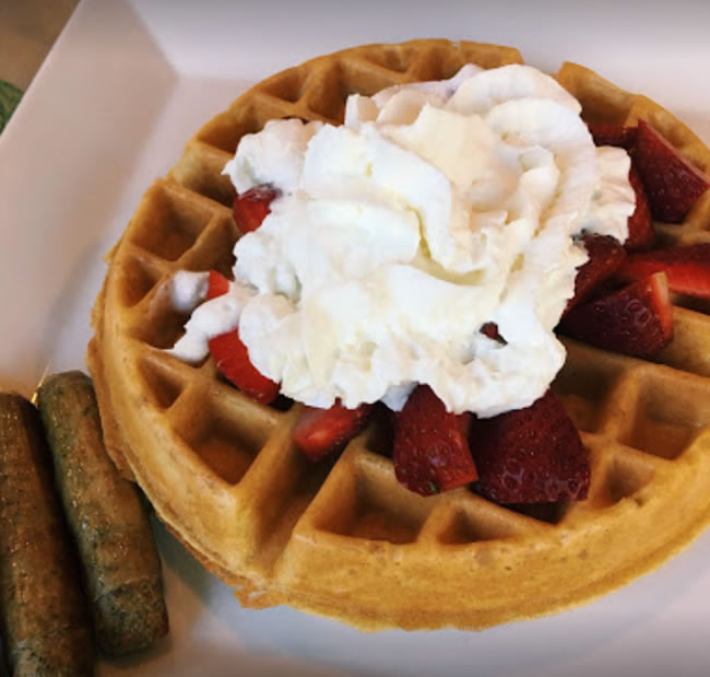 Belgian waffle topped with strawberries and whipped cream with two sausage links