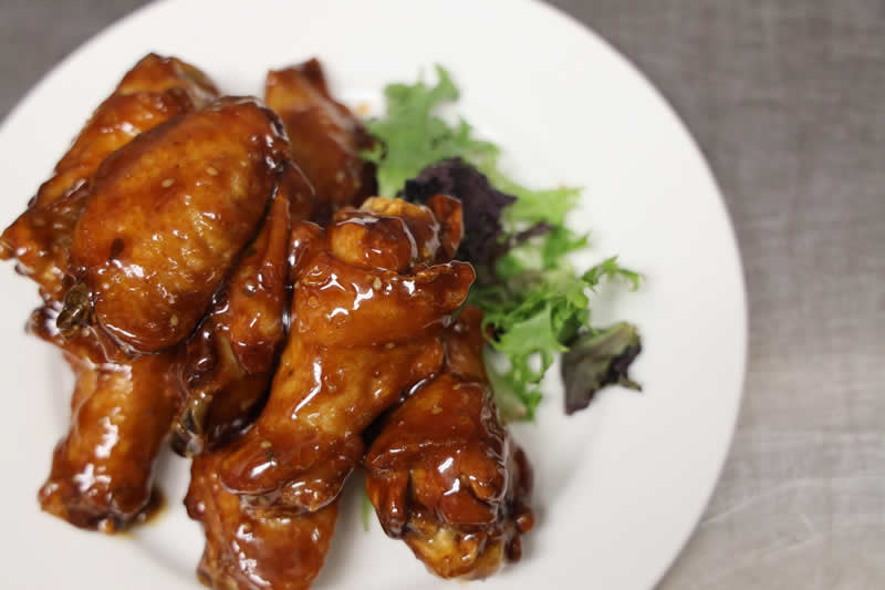 a plate of chicken wings on a bed of greens