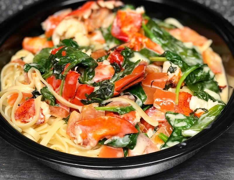 Plate of Lobster Florentine, sautéed lobster meat and tail in a rich cream sauce with tomatoes, fresh spinach and basil, tossed with linguini